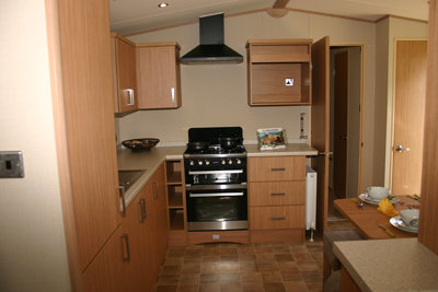 A twin cavity oven and extractor hood are standard appliances