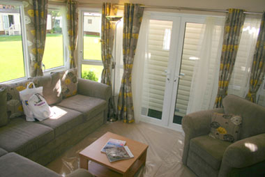 Lounge furniture comprises fixed seating plus an armchair and coffee table. The patio doors in the end wall are an optional extra.